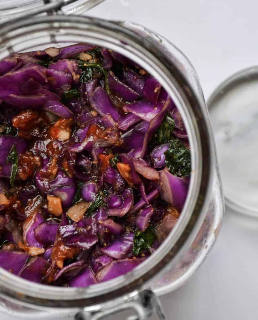 Top down view of Nasturtiums kimchi in a glass jar sitting on a white bench