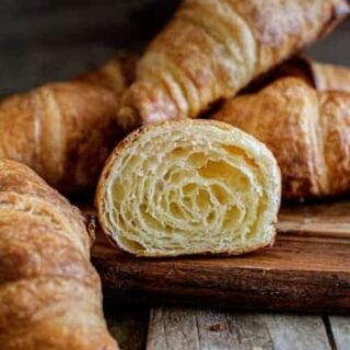 a cut croissant on a wooden board with whole croissants around it