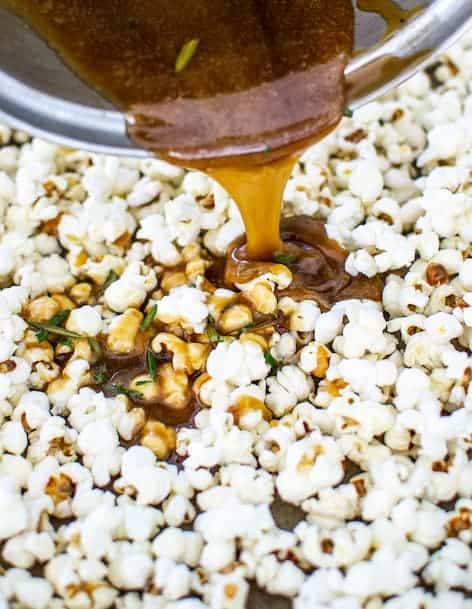 caramel in a saucepan being drizzled over popcorn with rosemary