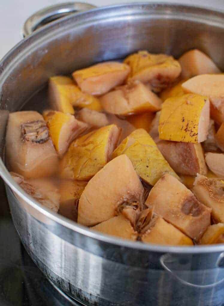 Cooked quince pieces in water in a silver pot