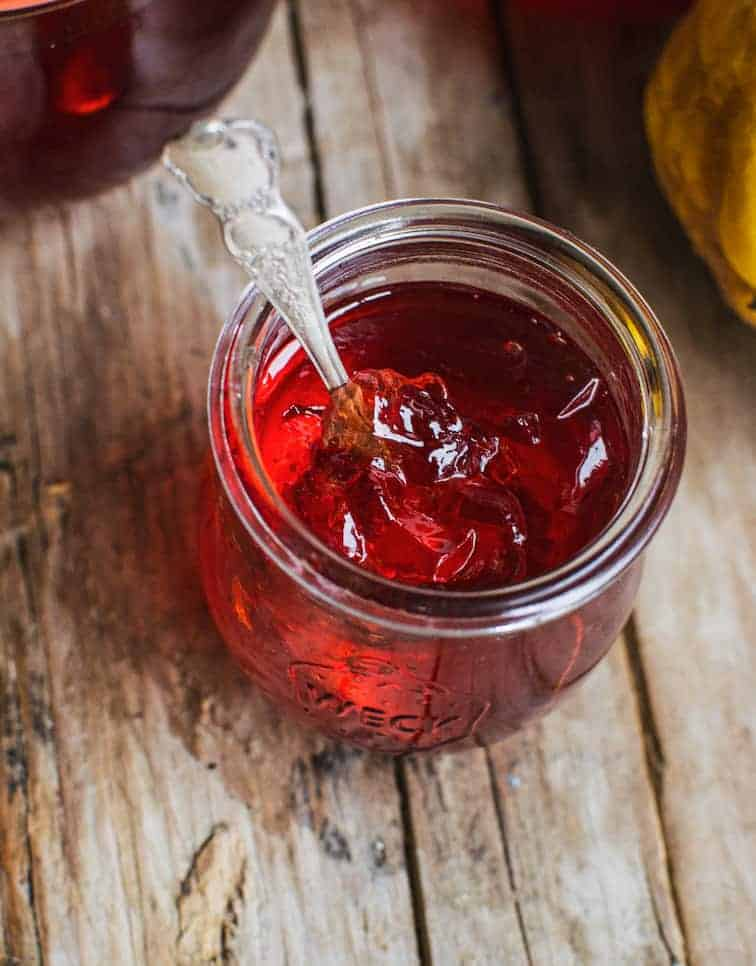 A jar of red quince jelly on a wooden board with a spoon in it