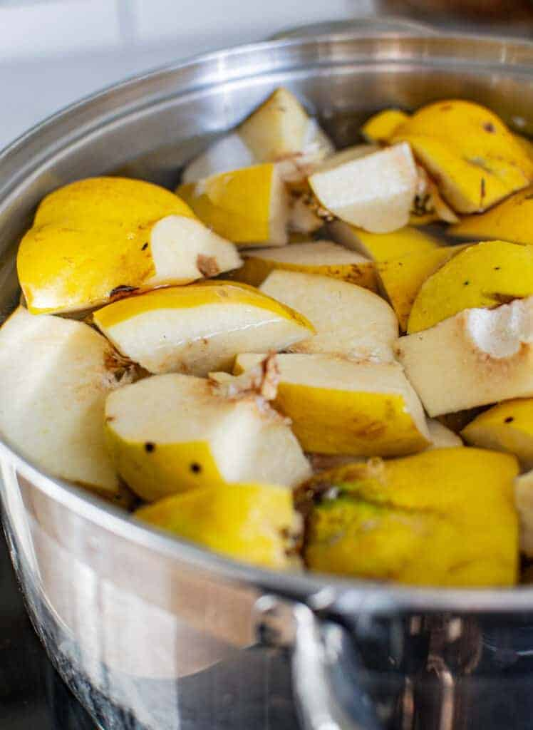 quince pieces simmering in water in a silver pot