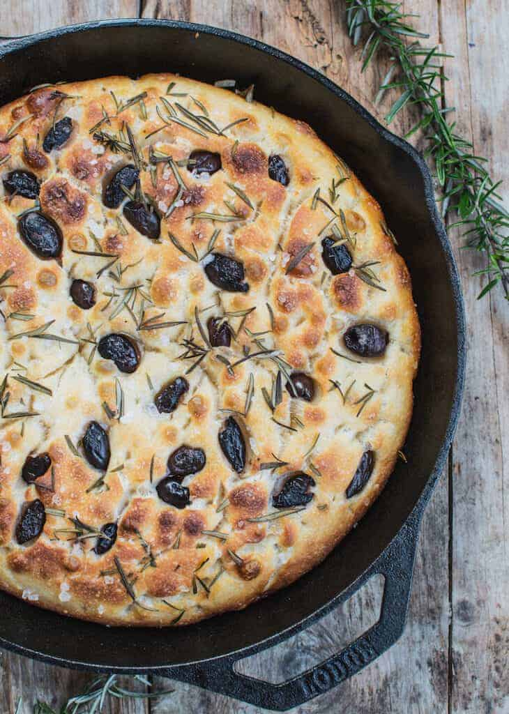 a cast iron pan with focaccia bread in it