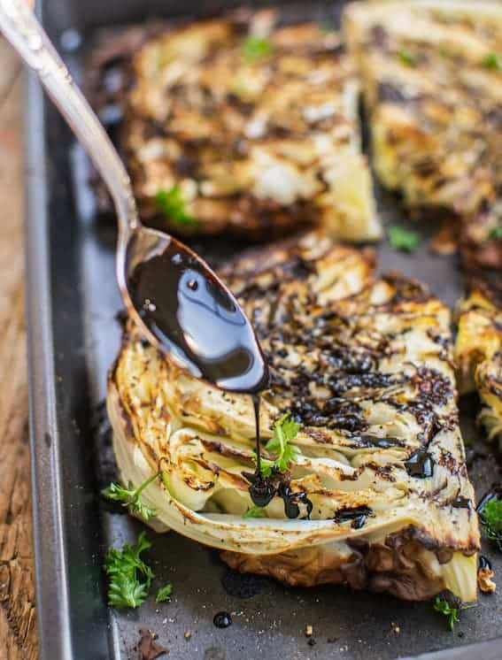 Roasted cabbage steaks drizzled with balsamic reduction, side view