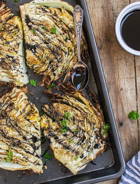 Roasted cabbage steaks drizzled with balsamic reduction, bird's eye view