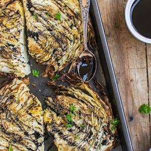 a tray of roasted cabbage on a wooden bench drizzled with balsamic