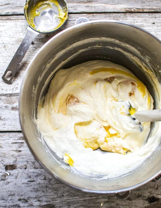 lemon curd mixed into yogurt with a  spatula inside a steel bowl sitting on a wooden table