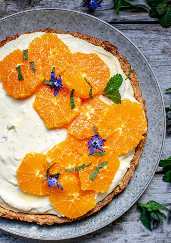 top down view of a lemon yogurt tart with slices of orange and mint on top, sitting on a grey plate