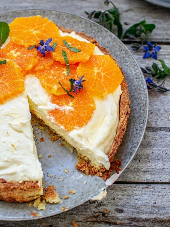 lemon yogurt tart with sliced oranges and mint on top, with one slice missing on a grey plate and on top of a wooden table