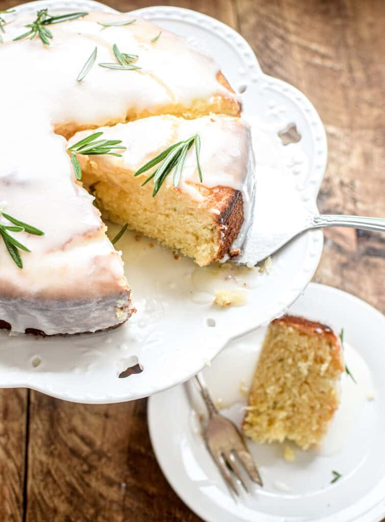 a close up of a yellow lemon cake with white icing and green fresh rosemary