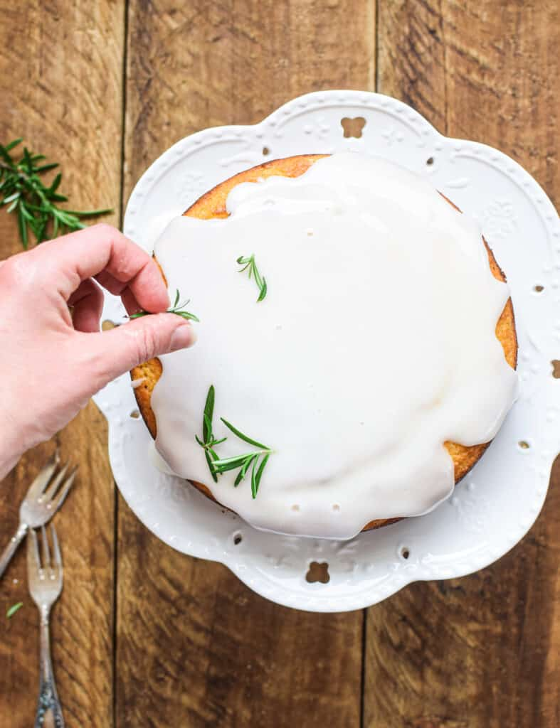 rosemary sprigs being garnished on the cake
