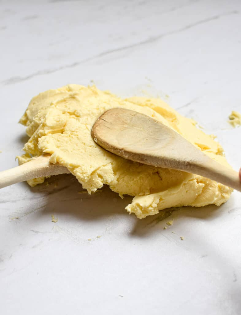 two wooden spoons kneading butter to remove buttermilk