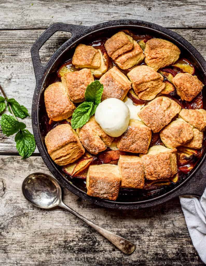 birds eye view of a skillet peach cobbler with sourdough starter biscuits on a wooden board with fresh mint