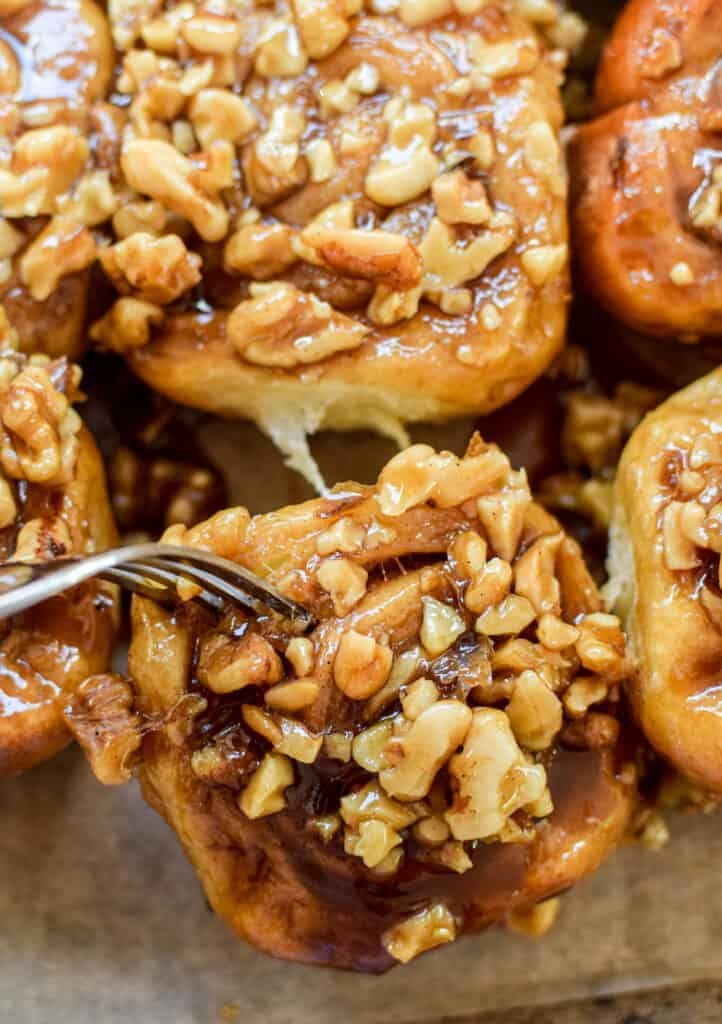 A sourdough sticky bun being pulled away by a fork. Topped with walnuts and sticky caramel