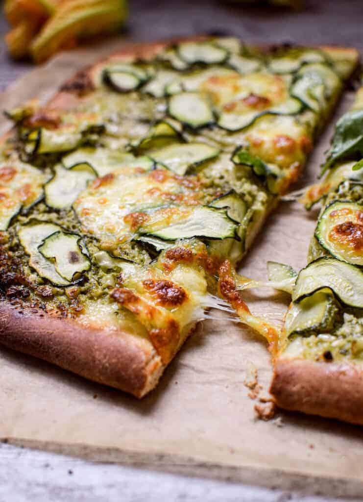 a side view of a zucchini pesto pizza, a piece being picked up with melted cheese stretching off it