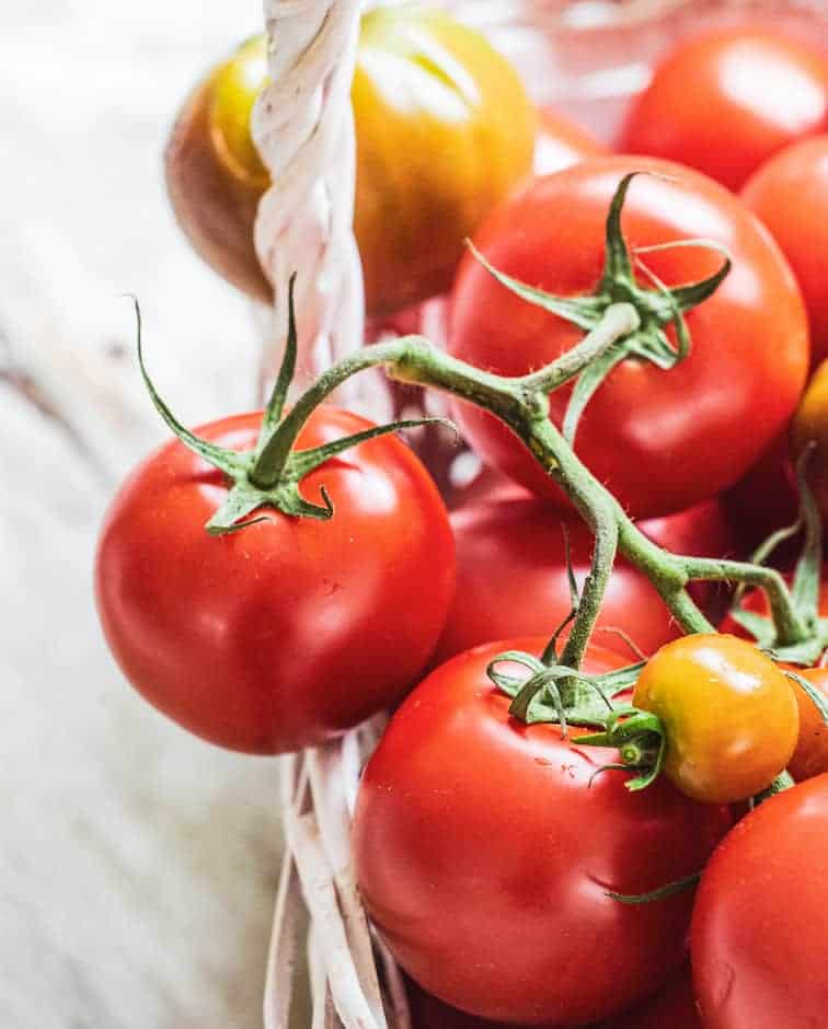 Close up of white basket filled with red on the vine tomatoes and 1 yellow cherry tomato on top. 1 yellow tomato in the background.