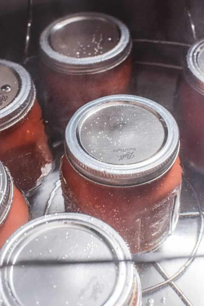6 jars of tomatoes with lids sitting in a large pot with an almost boiling water bath covering the jars.