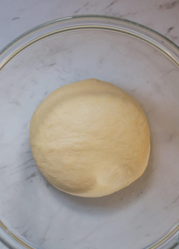 dough in a ball within a glass bowl on a white bench