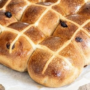 baked hot cross buns on parchment paper