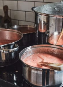 3 saucepans of passata being cooked on the stove