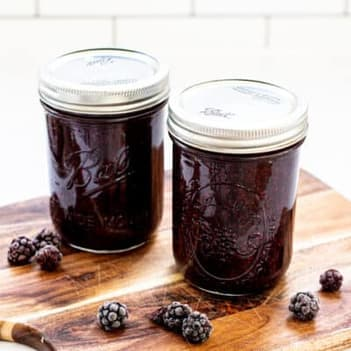 two jars of blackberry jam on a wooden board