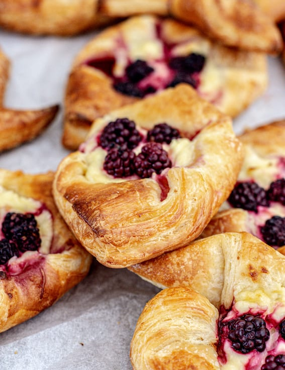 a pile of sourdough pastries on baking paper. The pastries all have blackberries and cream cheese on them