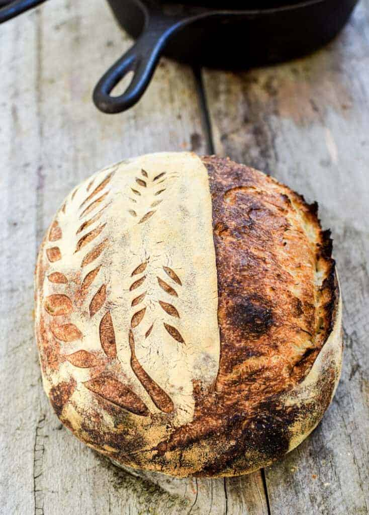 A sourdough loaf on a wooden board with a cast iron pot in the background. The loaf has patterns scored into it on one side