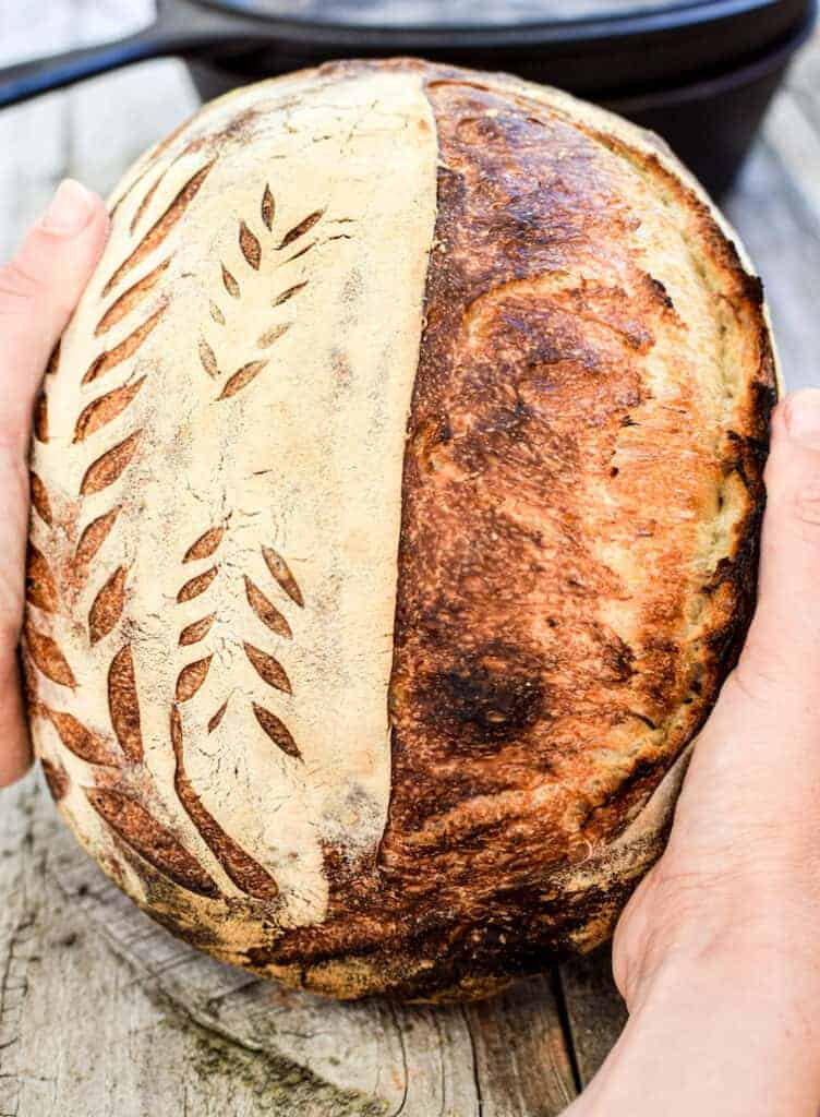 two hands holding a loaf of bread with patterns scored into it. In the background is a cast iron pot out of focus