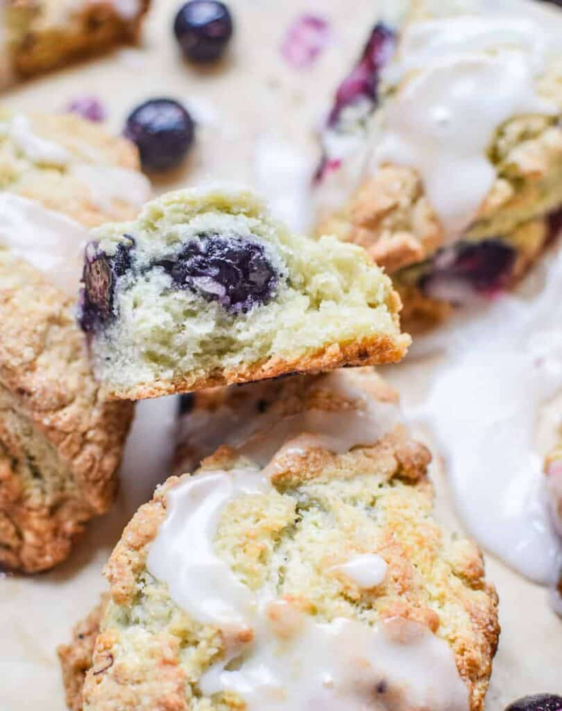 Blueberry scones with white icing sugar drizzled over the sourdough scones