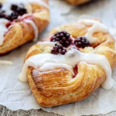 A close up of a pastry with 4 blackberries on it, on baking paper and drizzled with white icing