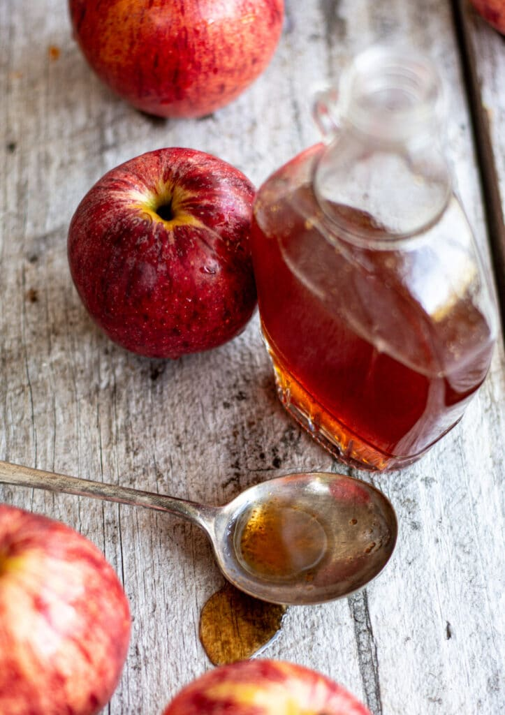 homemade apple syrup in a bottle and a spoon part filled with syrup on a wooden table with 3 red apples