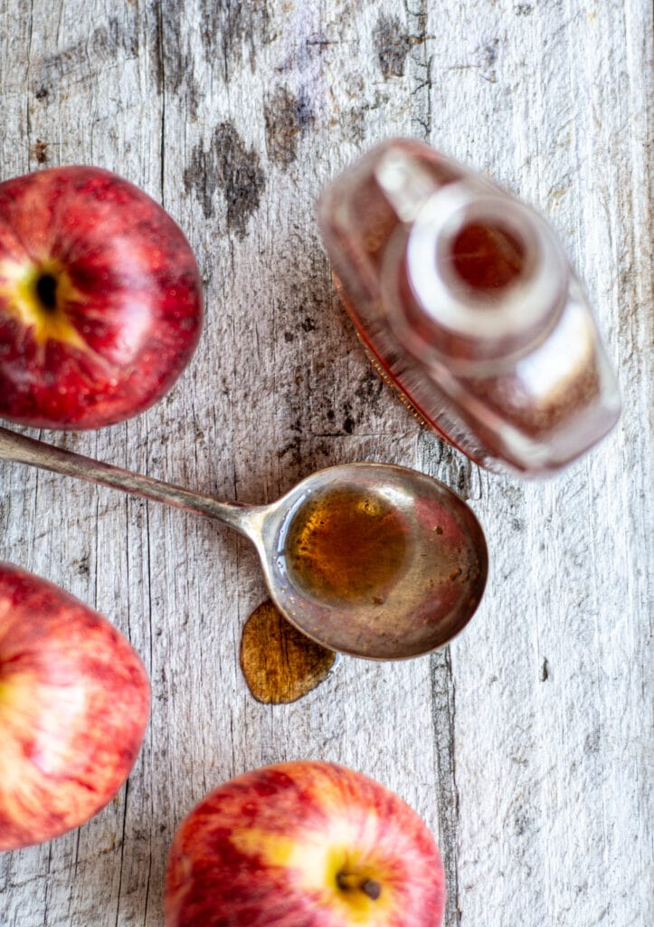 a birds eye view of apple syrup on a wooden bench with 3 red apples