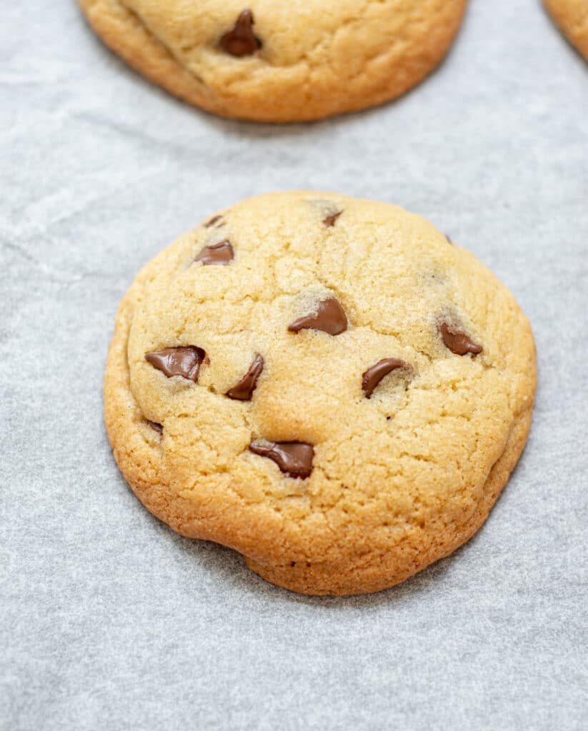 a close up of a baked chocolate chip cookie on white parchment paper
