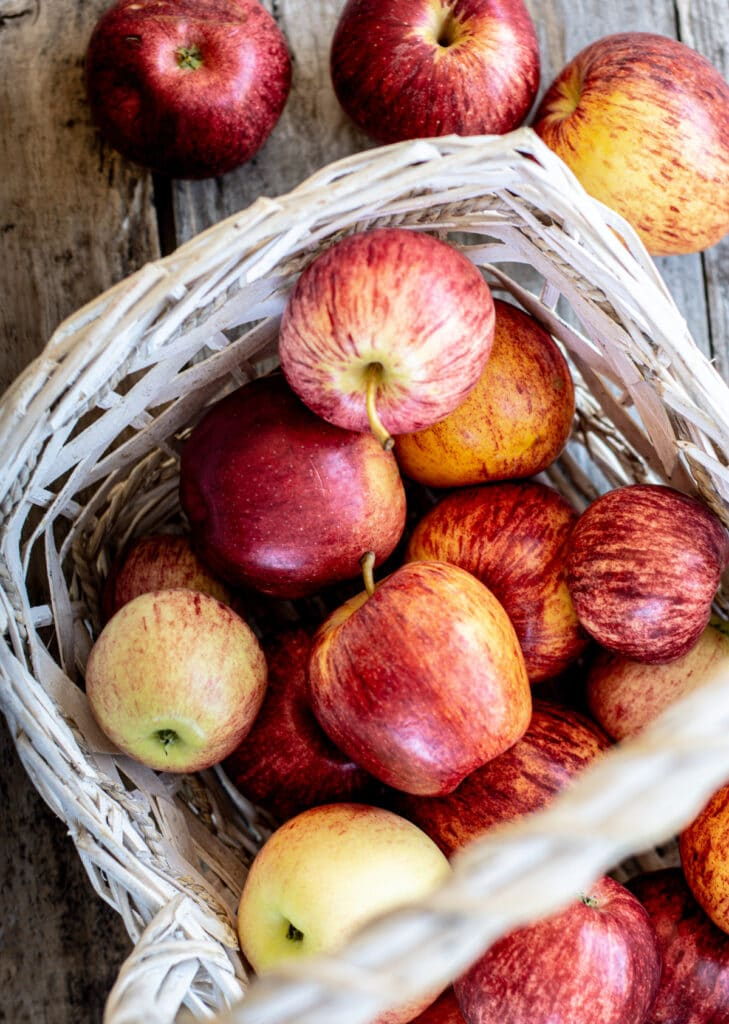 birds eye view of a white basket of red apples sitting on a wooden table