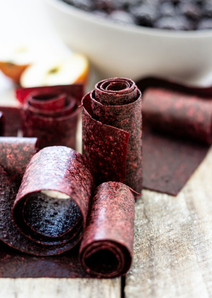 fruit leather rolls on a wooden board with a bowl of berries in the background