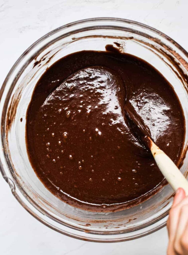 A glass bowl of chocolate Cake batter being stirred with a spatula