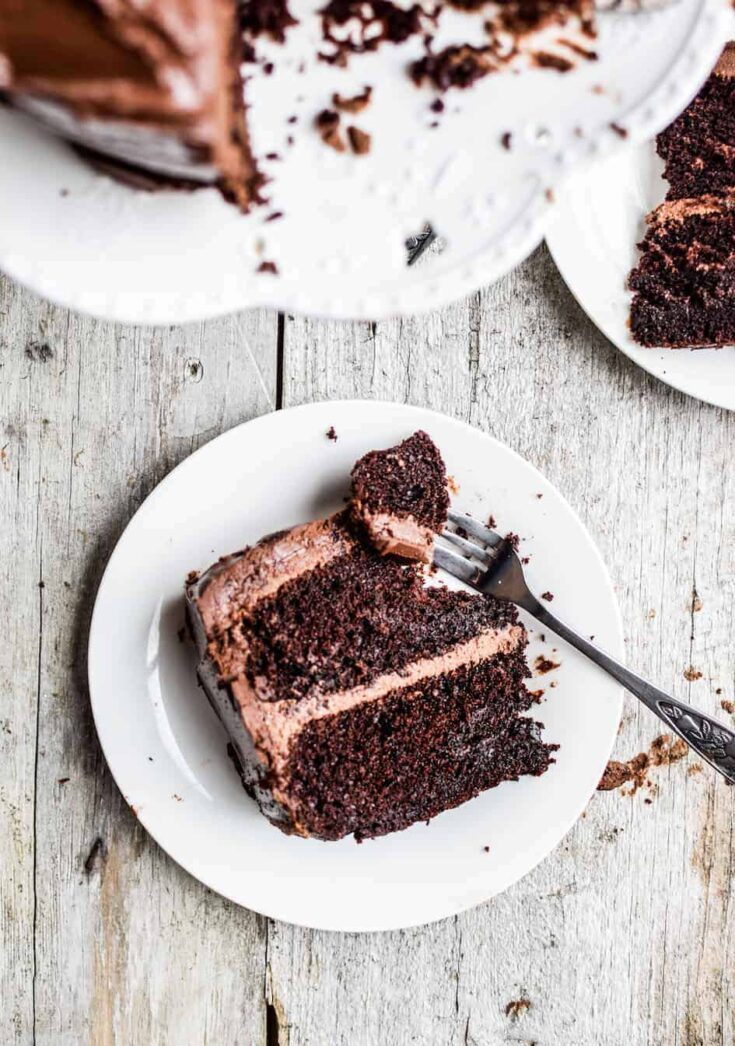 a slice of sourdough chocolate cake with a piece removed with a fork on a white plate