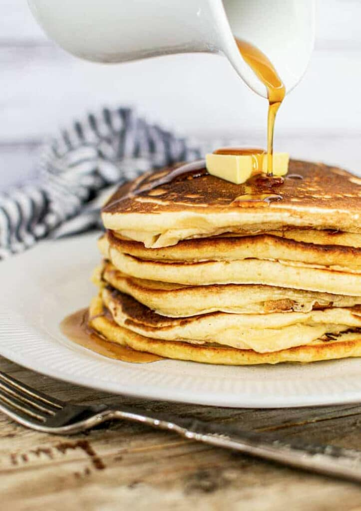 a stack of pancakes with a knob of butter and maple syrup being poured over and a fork in the foreground