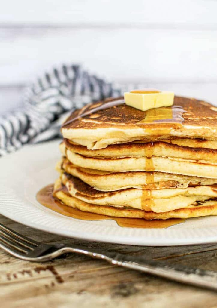 a stack of pancakes with a knob of butter on top on a white plate