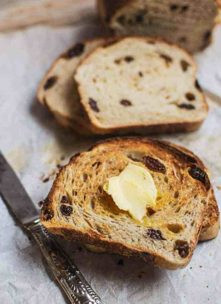 sliced and buttered sourdough raisin bread on baking paper