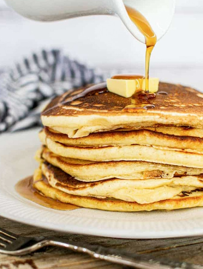 a stack of pancakes with a knob of butter and maple syrup being poured over