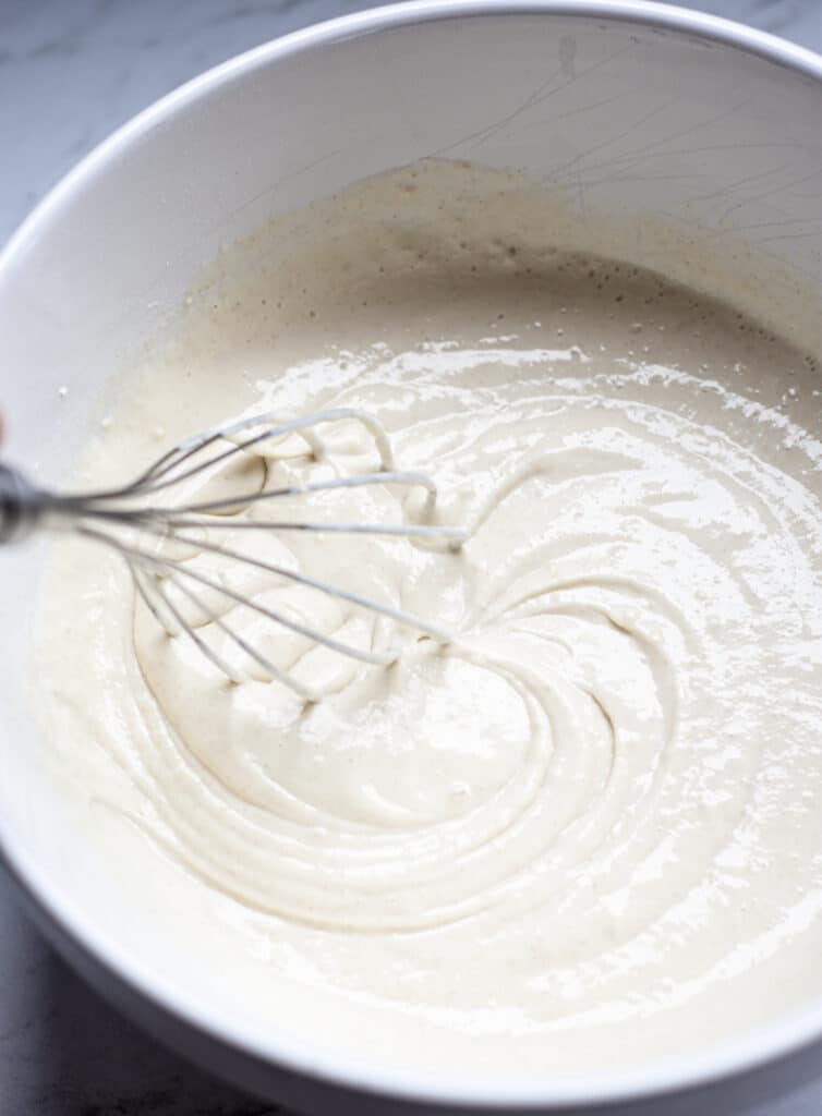 a bowl of pancake batter with a whisk