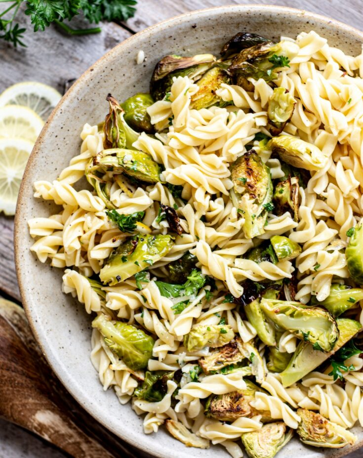 a bird' eye view of a bowl of fusilli pasta with roasted Brussels sprouts and lemon