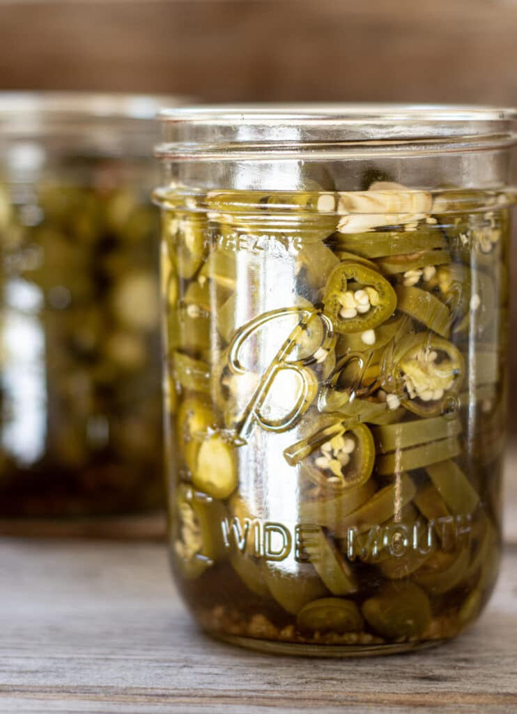 a close up of a glass jar of muted green jalapeño pepper slices on a wooden board.another jar is in the background