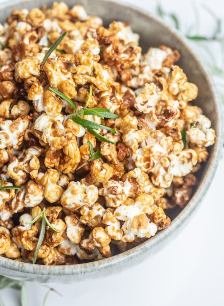 a close up of a bowl of caramel popcorn with green rosemary