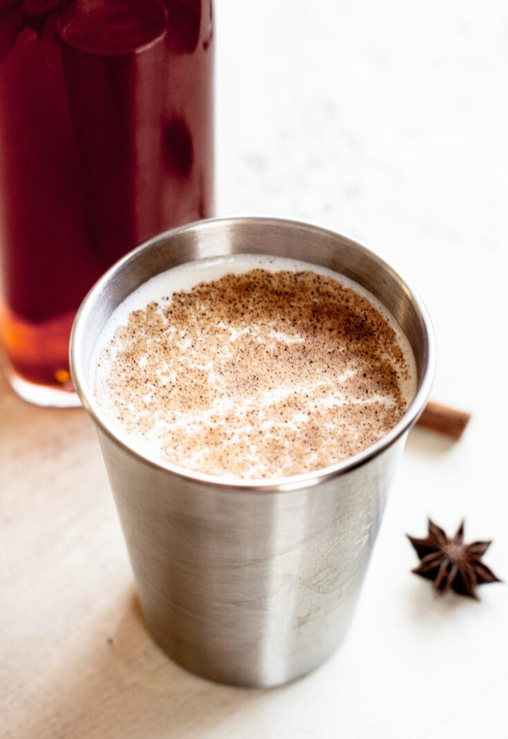 a close up f milky chai tea a cinnamon stick and star anise in the background