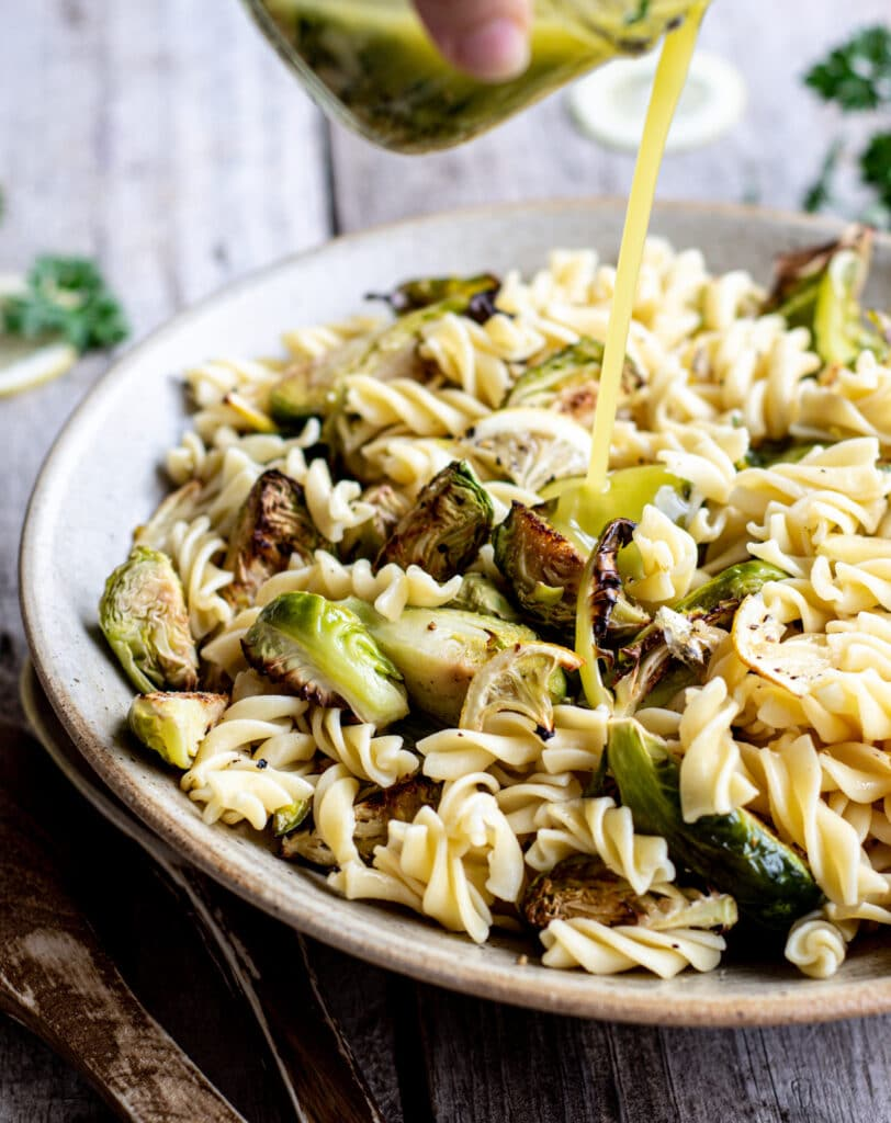 dressing being poured over a bowl of fusilli pasta with roasted Brussels sprouts and lemon