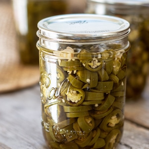 a glass jar of muted green jalapeño pepper slices on a wooden board. 2 other jars are in the background. Cropped picture