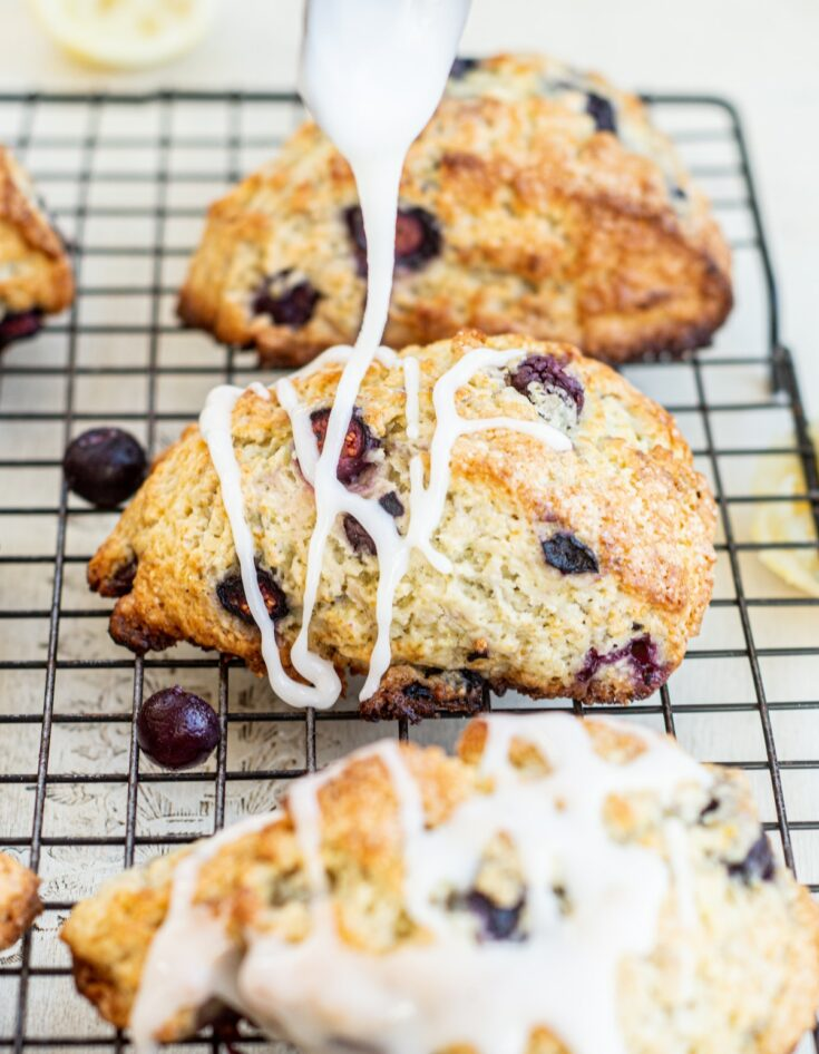 icing being drizzled onto sourdough blueberry scones
