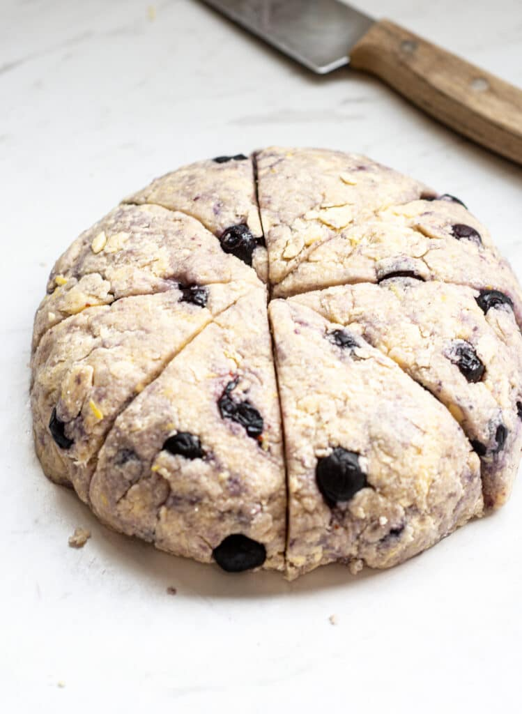 a circle of blueberry scone dough cut into 8 wedges